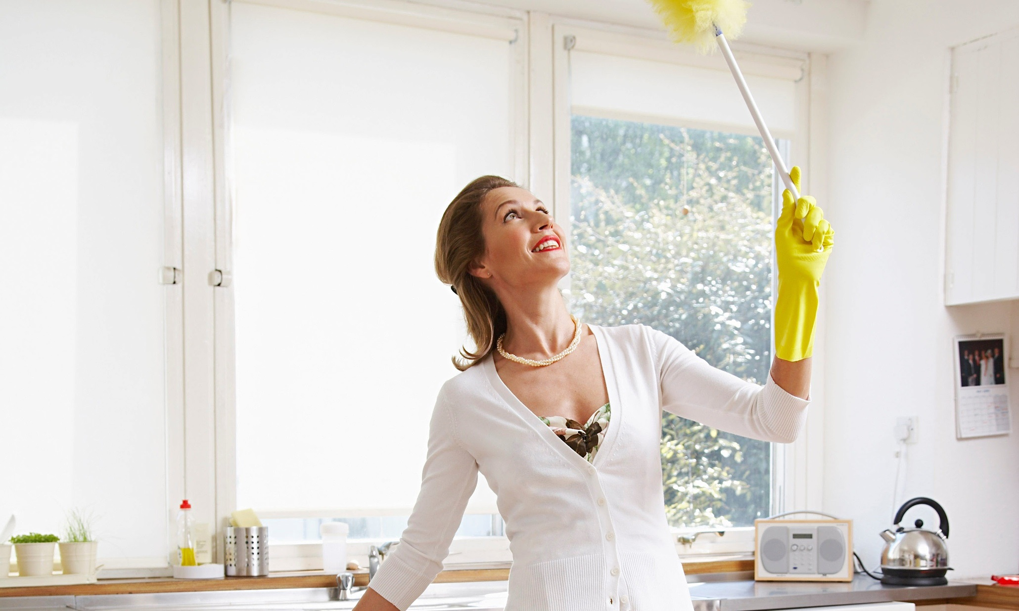 Woman dusting with gloves on, grinning, in a kitsch way