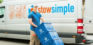 Young Delivery Man Holding Trolley With Stow Simple Boxes